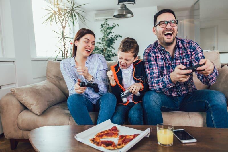 Família que senta-se em um sofá e que joga jogos de vídeo e que come a pizza imagens de stock royalty free