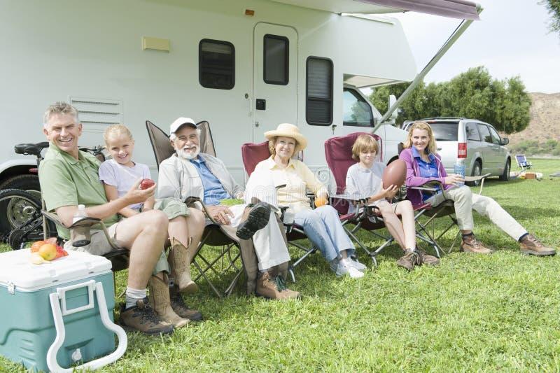 Família que senta-se fora da casa do rv fotografia de stock