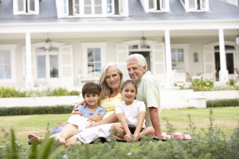 Família que senta-se fora da casa no gramado imagem de stock
