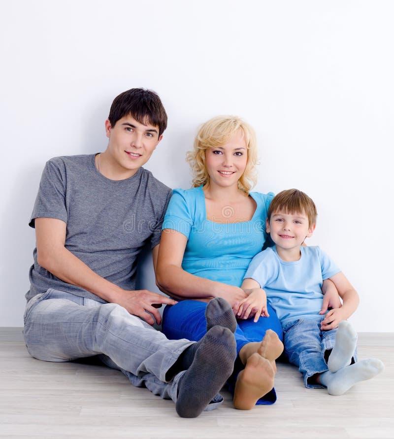 Família que senta-se junto no assoalho imagens de stock