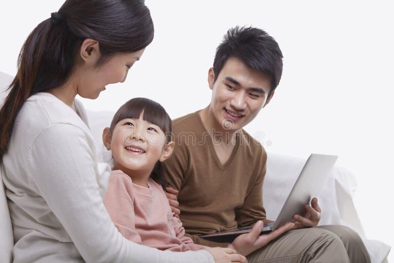 A família que senta-se junto no sofá usando o portátil, mãe está olhando sua filha de sorriso, tiro do estúdio fotografia de stock royalty free