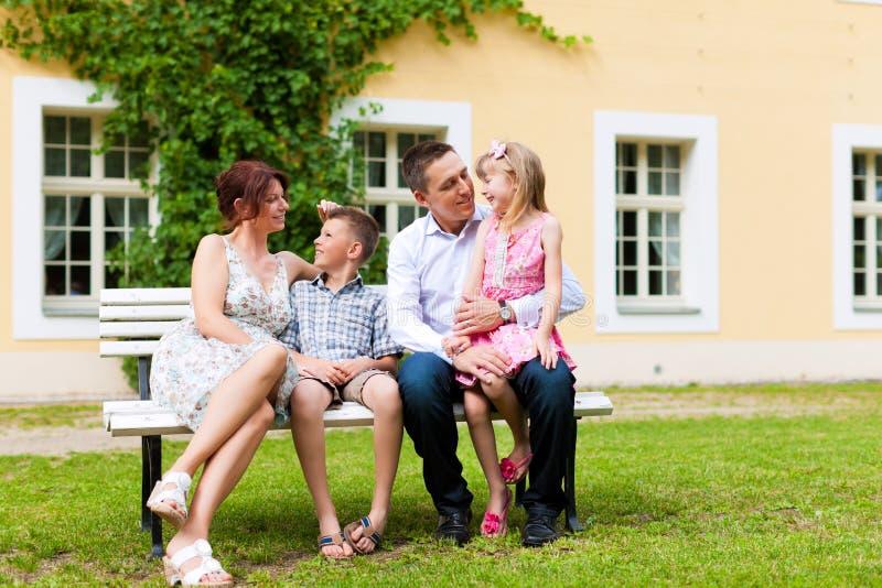 Família que senta-se na frente de sua HOME imagens de stock royalty free