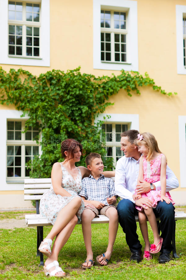 Família que senta-se na frente de sua HOME fotos de stock royalty free