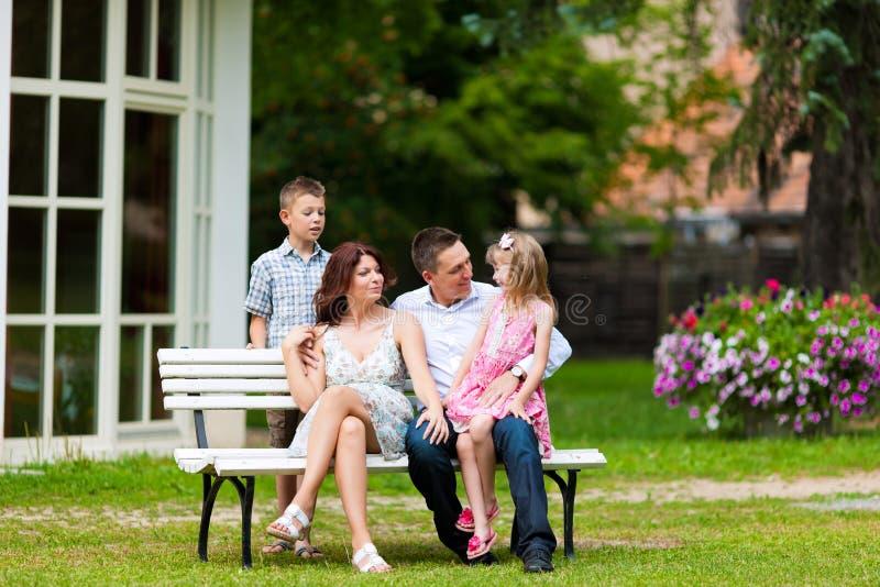 Família que senta-se na frente de sua HOME foto de stock royalty free