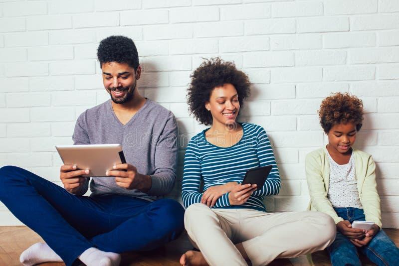 Família que senta-se na frente de uma parede de tijolo e que guarda uma tabuleta digital e telefones imagens de stock royalty free