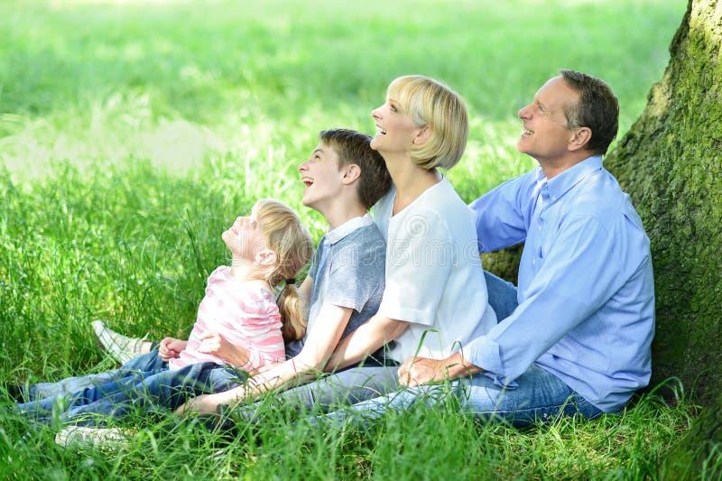 Família que senta-se na máscara sob a árvore fotografia de stock