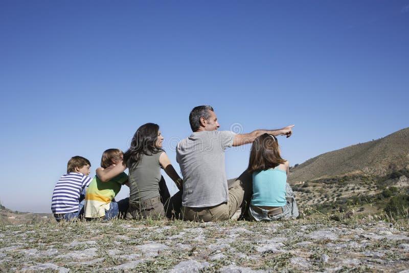 Família que senta-se na parte superior da montanha imagens de stock royalty free