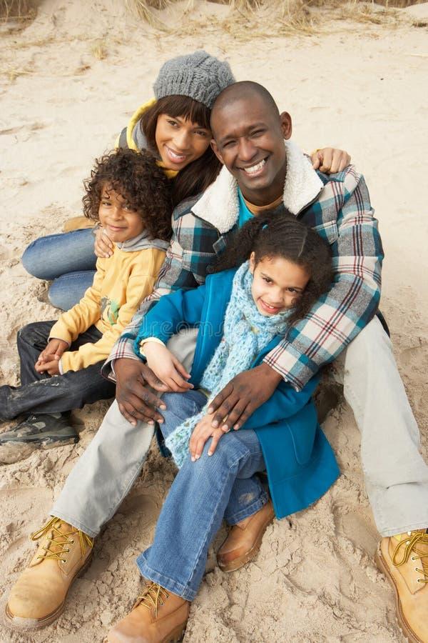 Família que senta-se na praia do inverno imagens de stock
