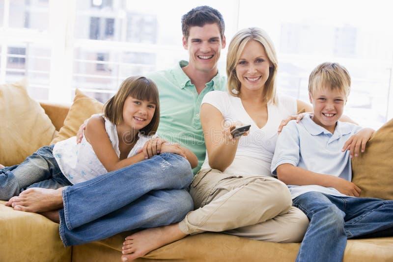 Família que senta-se na sala de visitas com de controle remoto
