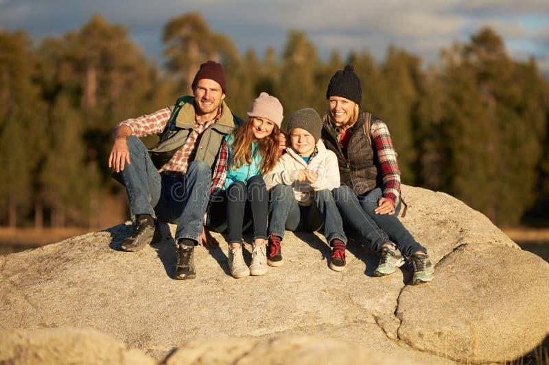 Família que senta-se no afloramento rochoso, Big Bear, Califórnia, EUA fotos de stock royalty free