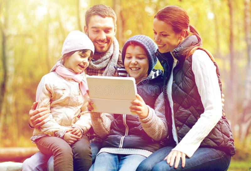 Família que senta-se no banco com o PC da tabuleta no acampamento imagens de stock
