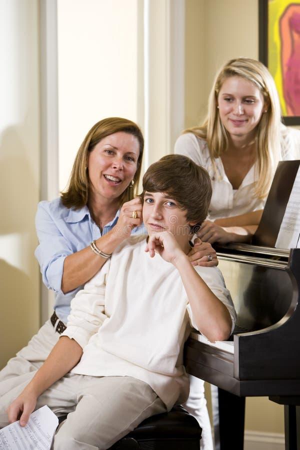 Família que senta-se no banco do piano, filho de arrelia da matriz fotografia de stock royalty free