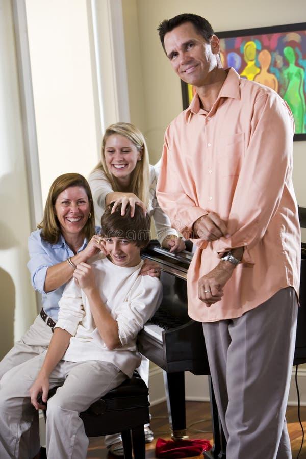 Família que senta-se no banco do piano, filho de arrelia da matriz imagem de stock