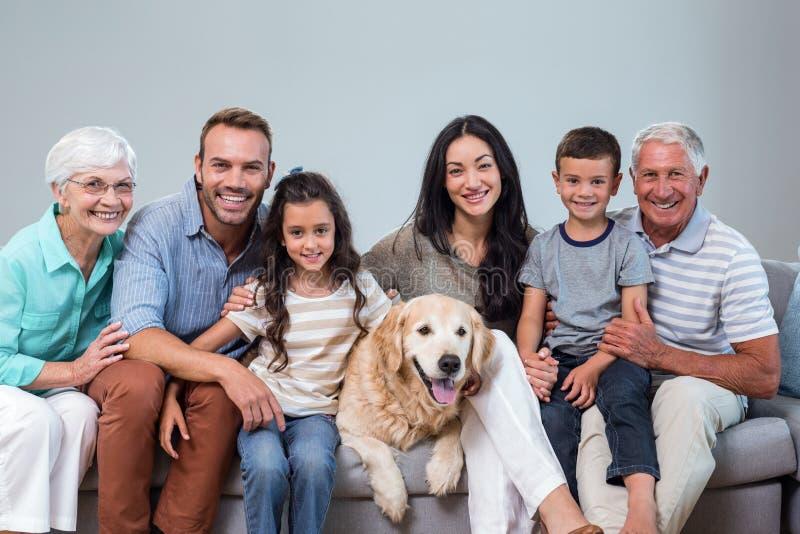 Família que senta-se no sofá com cão imagens de stock royalty free