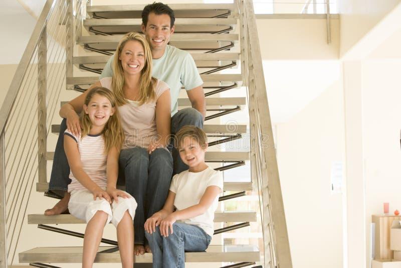Família que senta-se no sorriso da escadaria fotos de stock