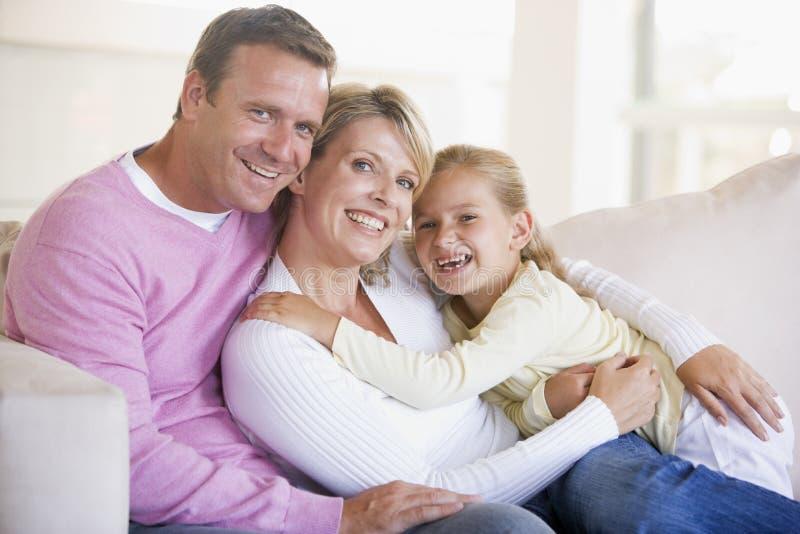 Família que senta-se no sorriso da sala de visitas fotos de stock royalty free