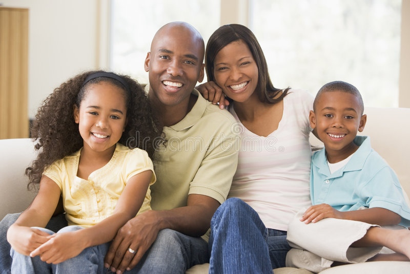 Família que senta-se no sorriso da sala de visitas foto de stock