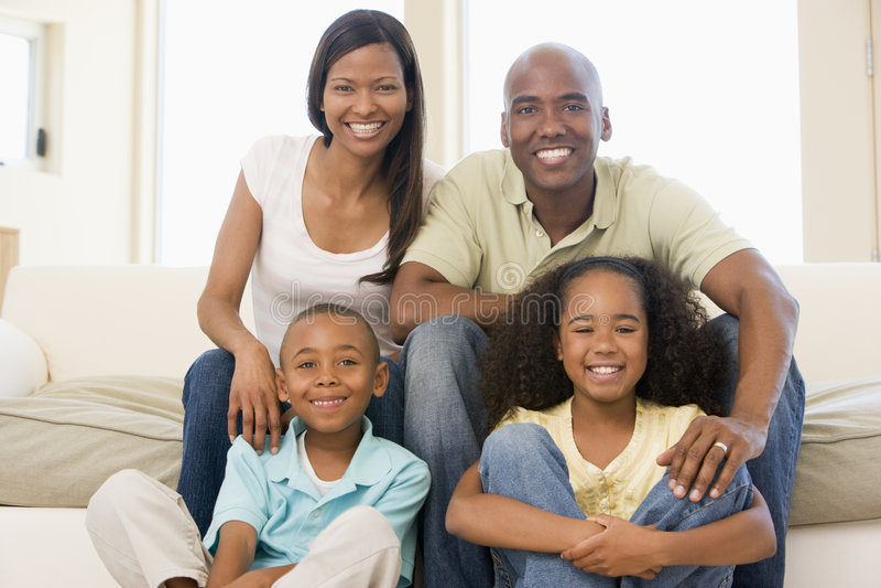 Família que senta-se no sorriso da sala de visitas fotografia de stock