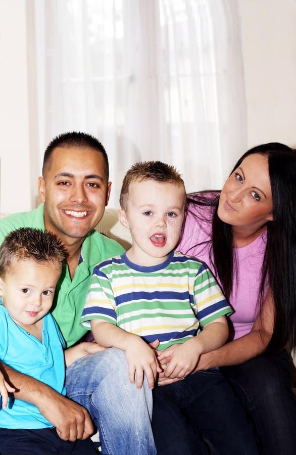 Família que senta-se no sorriso do sofá foto de stock royalty free