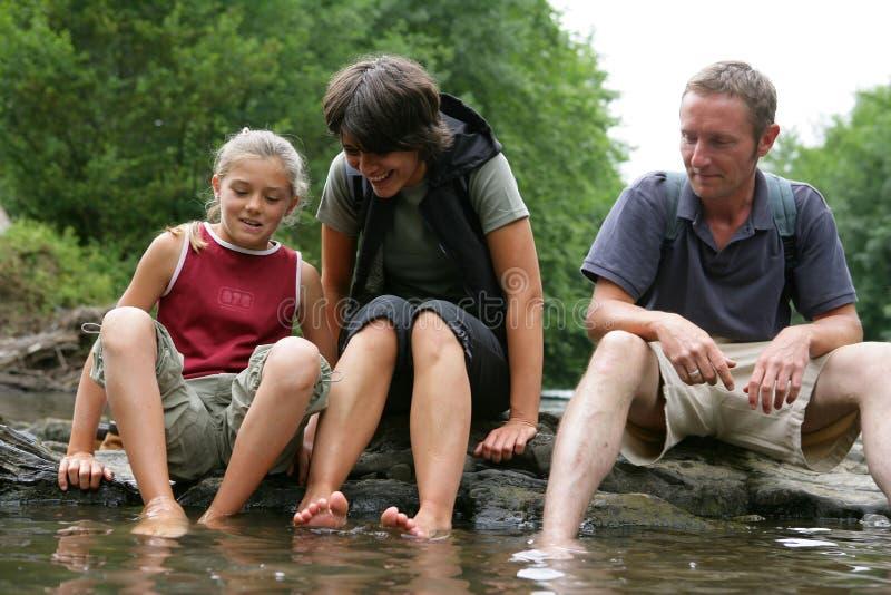 Família que senta-se pelo rio imagem de stock