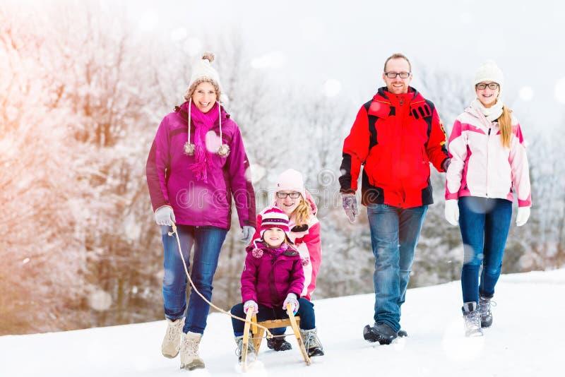 Família que tem a caminhada do inverno na neve com trenó fotos de stock