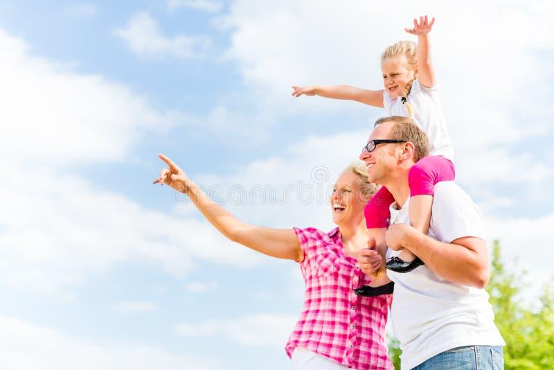 Família que tem a caminhada no prado fora imagem de stock