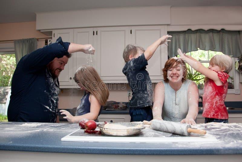 Família que tem a luta do alimento na cozinha fotos de stock