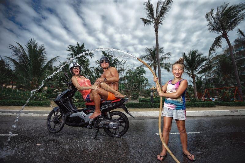 Família que tem o divertimento com a mangueira de jardim que espirra a chuva do verão fotografia de stock