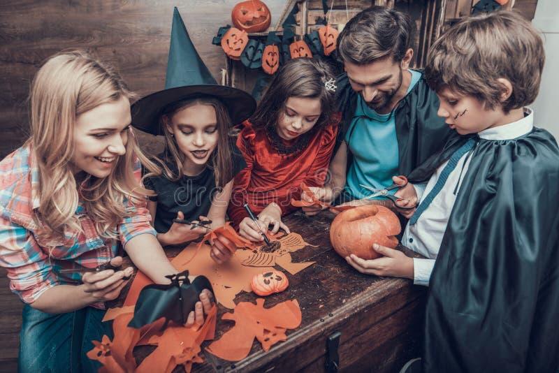 Família que tem o divertimento que faz decorações de Dia das Bruxas fotografia de stock royalty free