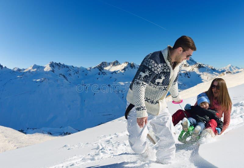 Família que tem o divertimento na neve fresca em férias do inverno fotografia de stock royalty free