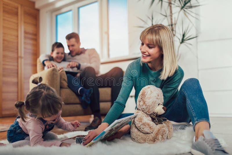 Família que tem o divertimento no assoalho na sala de visitas em casa, rindo fotos de stock royalty free