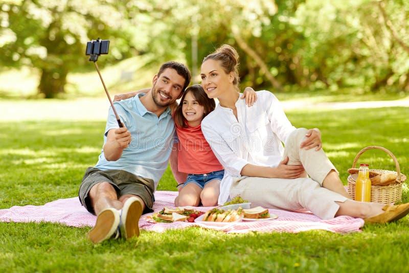 Família que tem o piquenique e que toma o selfie no parque imagem de stock royalty free