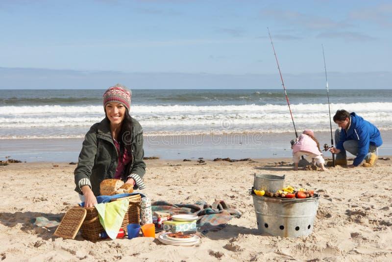 Família que tem o piquenique na praia do inverno fotografia de stock