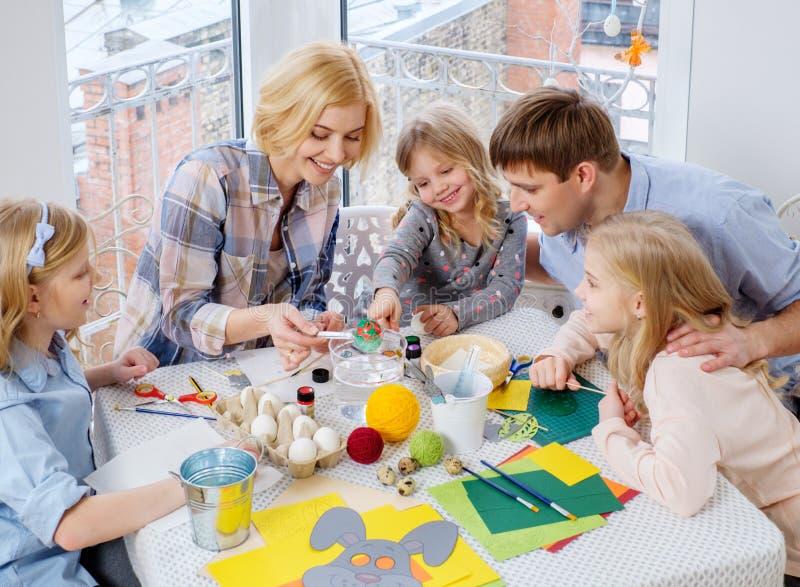 Família que tem a pintura do divertimento e que decora ovos da páscoa fotos de stock
