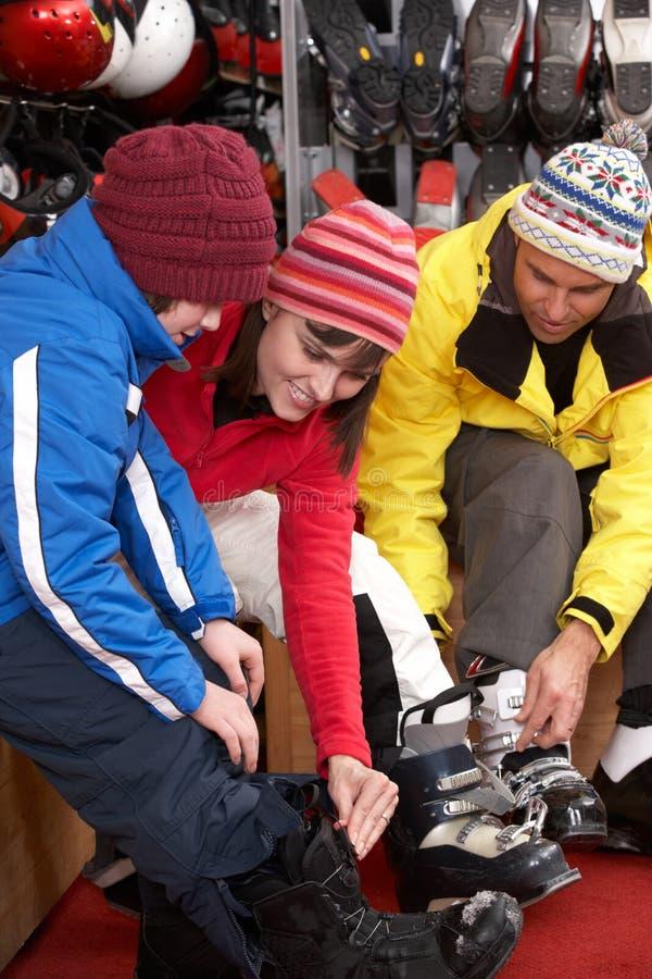 Família que tenta em carregadores de esqui na loja do aluguer foto de stock
