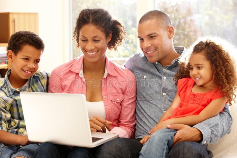 Família que trabalha no portátil em casa imagens de stock royalty free