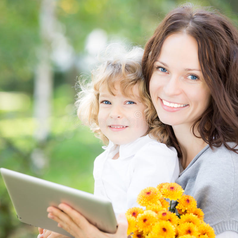 Família que usa o PC da tabuleta fora fotos de stock