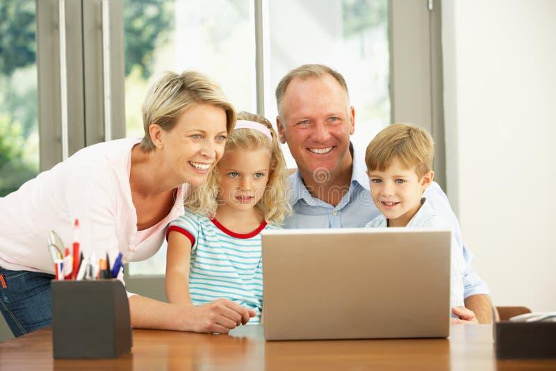 Família que usa o portátil em casa fotografia de stock