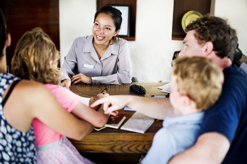 Família que verifica dentro no contador da reserva do recurso foto de stock royalty free