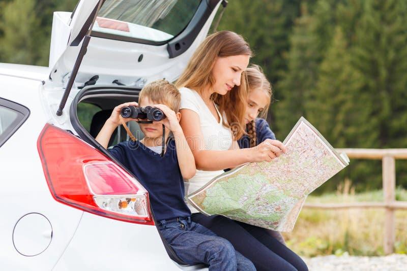 Família que viaja pelo carro e que usa o mapa para navegar foto de stock