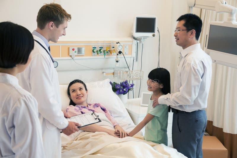 Família que visita a mãe no hospital, discutindo com o doutor imagens de stock