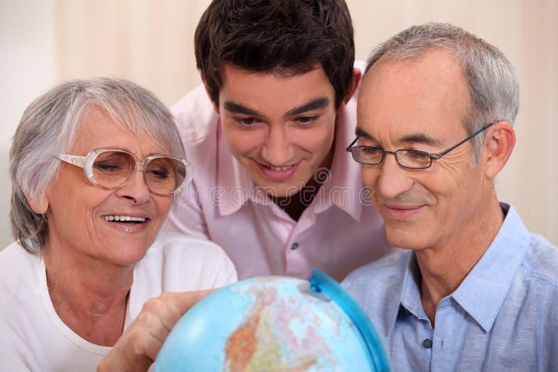 Família recolhida em torno do globo imagem de stock