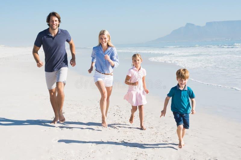 Família running na praia foto de stock