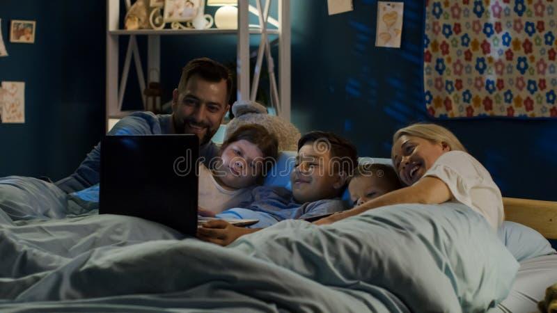 Família satisfeita que olha o filme engraçado no portátil imagens de stock