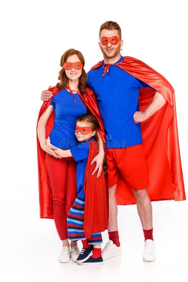 família super nas máscaras e nos casacos que estão junto e que sorriem na câmera fotografia de stock royalty free