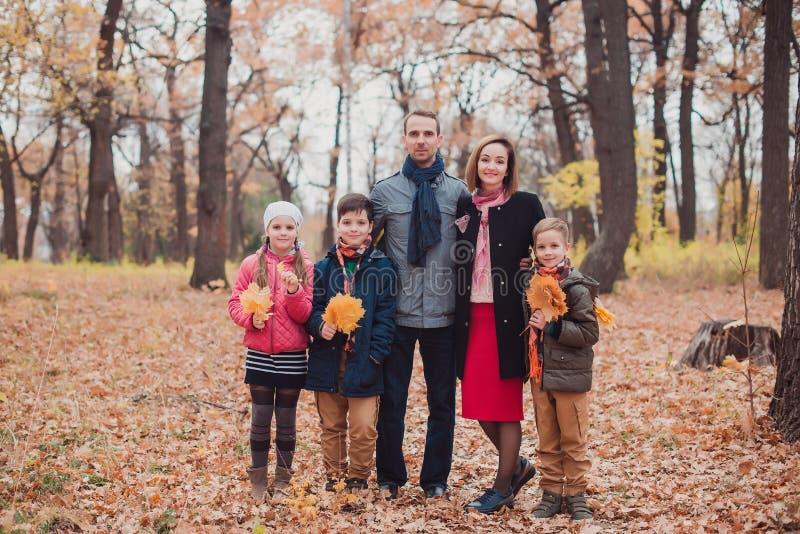 Família, três crianças na floresta, ficando nas folhas de outono fotos de stock