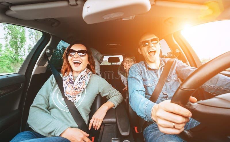 A família tradicional nova alegre tem uma auto viagem longa e o canto alto da música favorita junto Conceito do carro da equitaçã fotografia de stock royalty free