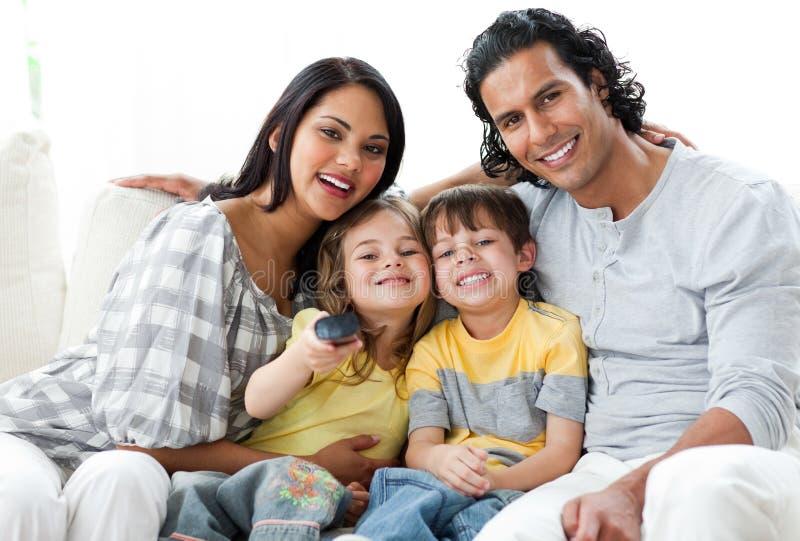 Família vívida que presta atenção à tevê junto