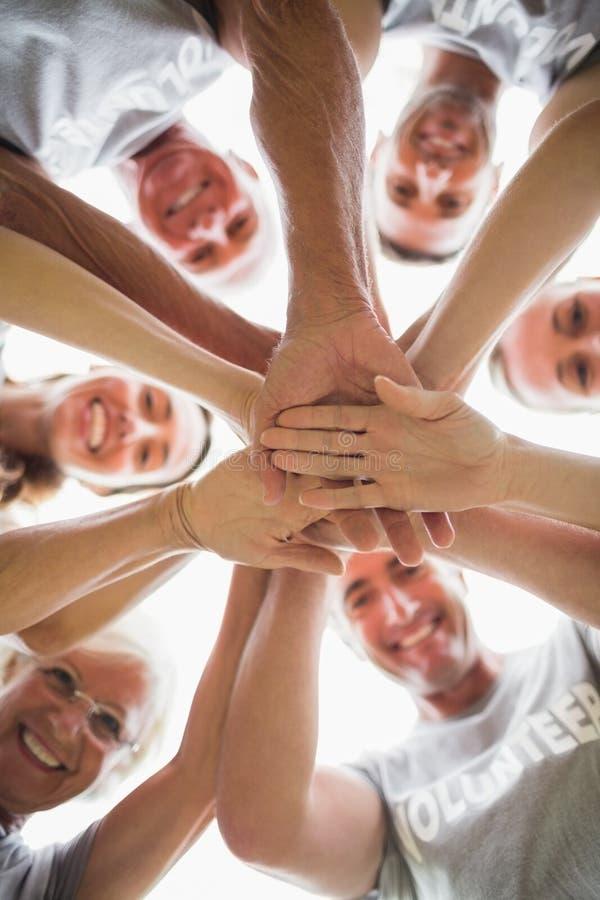 Família voluntária feliz que une suas mãos fotos de stock royalty free