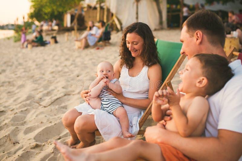 Fam?lia de quatro pessoas feliz caucasiano bonita nova que senta junto o abra?o no caf? da praia no por do sol da noite F?rias em fotos de stock royalty free